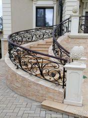Светлая лестница с эксклюзивными коваными ограждениями